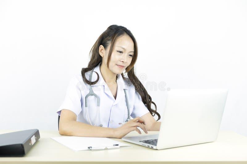 Χαμογελώντας ασιατικός γιατρός γυναικών που εργάζεται στο lap-top υπολογιστών στοκ φωτογραφία