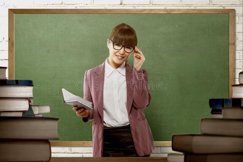Χαμογελώντας ασιατικός θηλυκός δάσκαλος έτοιμος να διδάξει στοκ εικόνα με δικαίωμα ελεύθερης χρήσης