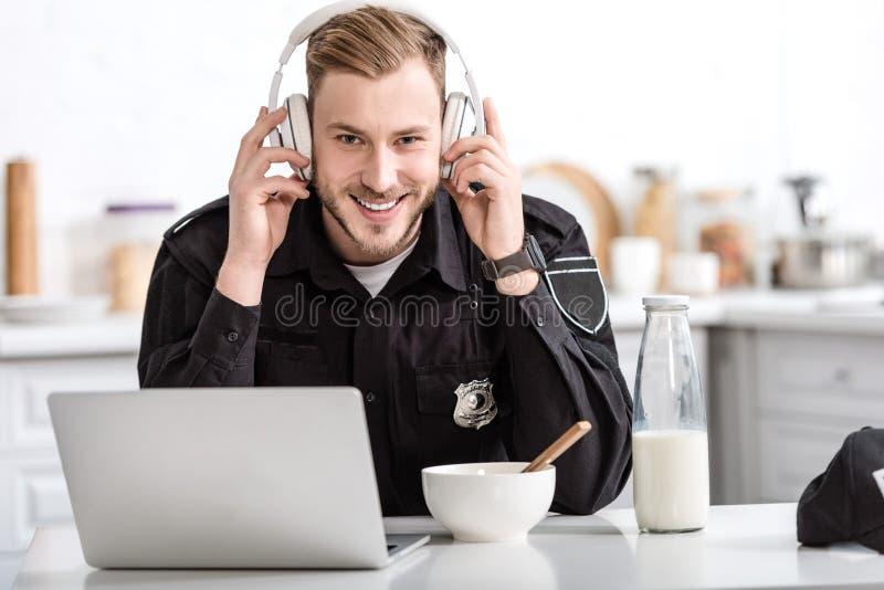 χαμογελώντας αστυνομικός που έχει το πρόγευμα και που ακούει τη μουσική με τα ακουστικά στοκ εικόνες με δικαίωμα ελεύθερης χρήσης