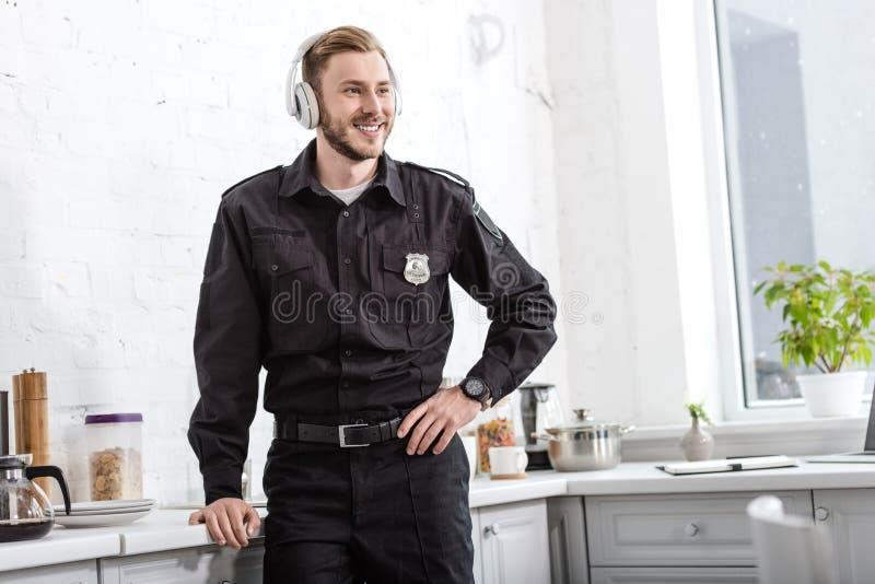 χαμογελώντας αστυνομικός που ακούει τη μουσική με τα ακουστικά στοκ εικόνα με δικαίωμα ελεύθερης χρήσης
