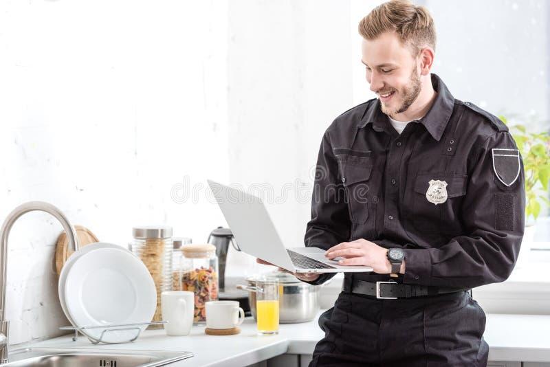 χαμογελώντας αστυνομικός που στέκεται και που χρησιμοποιεί το lap-top στοκ φωτογραφία