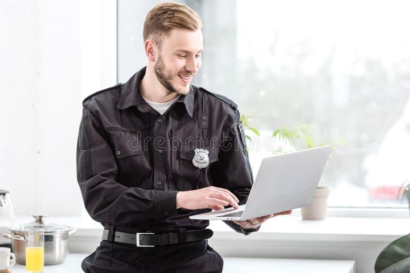 χαμογελώντας αστυνομικός που στέκεται και που χρησιμοποιεί το lap-top στοκ εικόνες με δικαίωμα ελεύθερης χρήσης