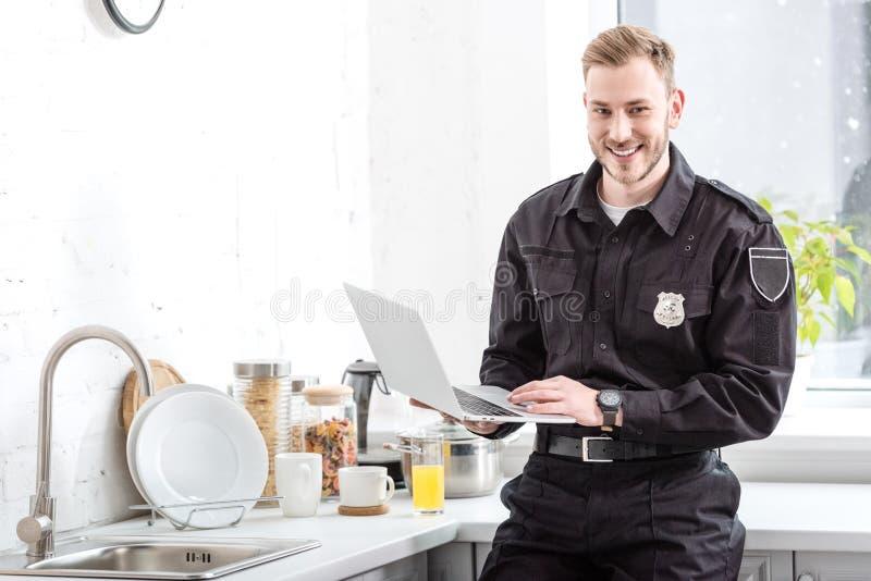 Χαμογελώντας αστυνομικός που στέκεται με το lap-top στοκ φωτογραφίες με δικαίωμα ελεύθερης χρήσης