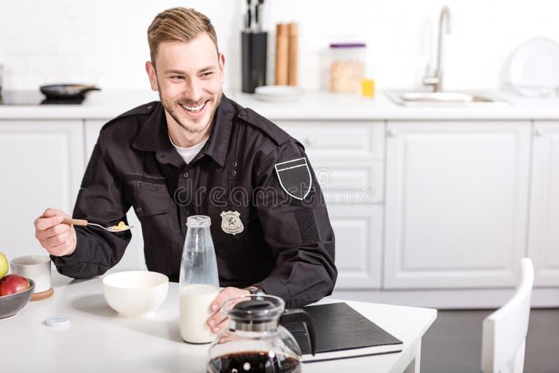 χαμογελώντας αστυνομικός που τρώει τα δημητριακά με το γάλα στοκ φωτογραφία με δικαίωμα ελεύθερης χρήσης