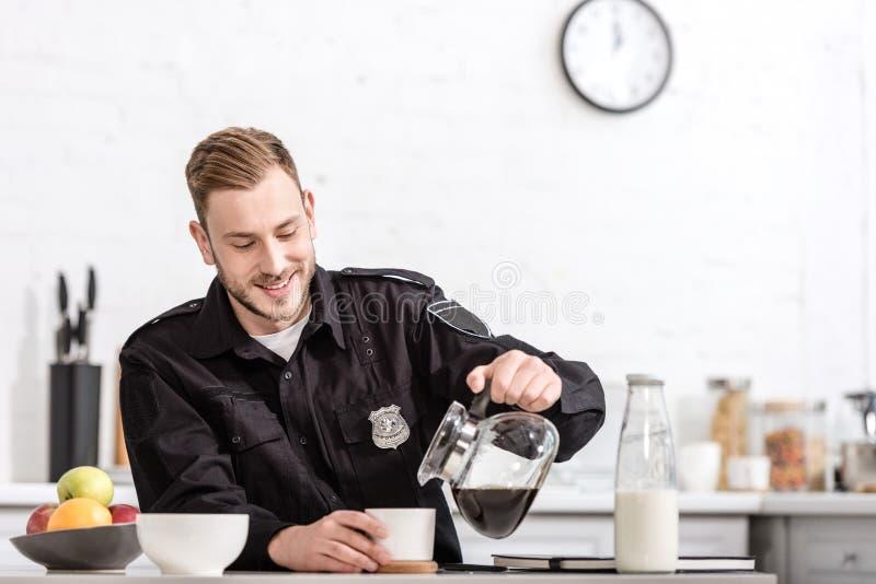 χαμογελώντας αστυνομικός που χύνει το φιλτραρισμένο καφέ από το δοχείο γυαλιού στοκ φωτογραφίες
