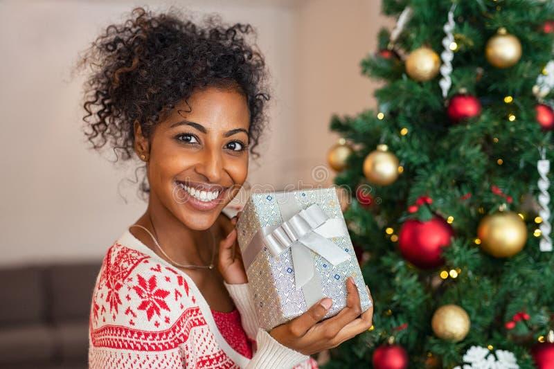 Χαμογελώντας αφρικανική γυναίκα με το χριστουγεννιάτικο δώρο στοκ φωτογραφία