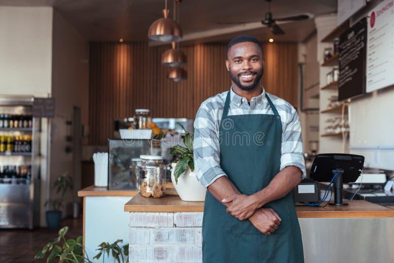 Χαμογελώντας αφρικανικός επιχειρηματίας που στέκεται στο μετρητή του καφέ του στοκ φωτογραφίες
