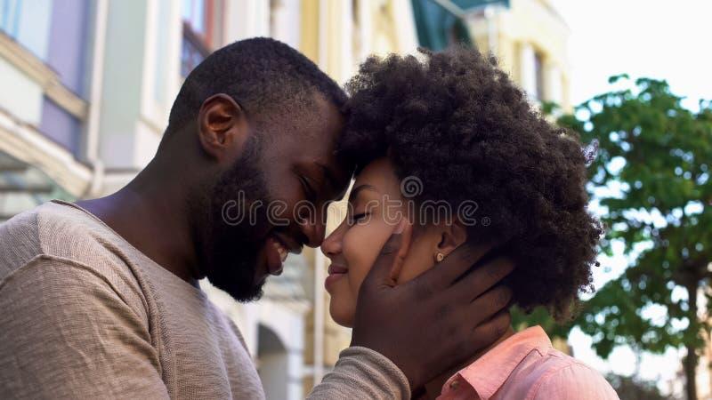 Χαμογελώντας αφρικανικό ζεύγος που σπρώχνει με τη μουσούδα, αγαπώντας ζεύγος που αγκαλιάζει, υπαίθρια ρομαντική ημερομηνία στοκ εικόνα με δικαίωμα ελεύθερης χρήσης