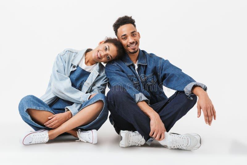 Χαμογελώντας αφρικανικό ζεύγος στα πουκάμισα τζιν που κάθεται μαζί στο πάτωμα στοκ εικόνες
