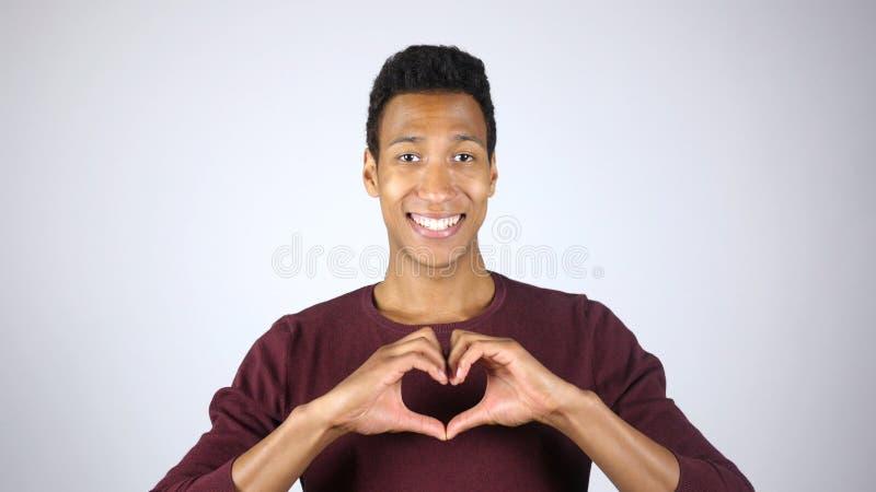 Χαμογελώντας αφροαμερικανός άτομο που κάνει τη μορφή καρδιών με το χέρι, που εκφράζουν την αγάπη, Gestu στοκ φωτογραφίες
