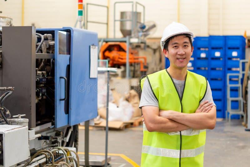 Χαμογελώντας βιομηχανικός εργάτης με την ασφάλεια σκληρή στις βιομηχανικές εγκαταστάσεις στοκ εικόνα