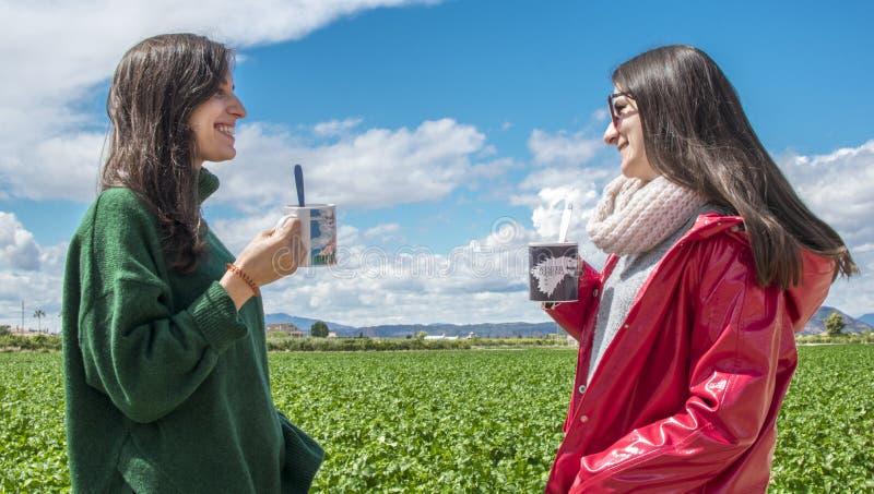 Χαμογελώντας γελώντας νέες γυναίκες που έχουν τη διασκέδαση πίνοντας τον καφέ και να κουβεντιάσει υπαίθριους Άνθρωποι, επικοινωνί στοκ εικόνες