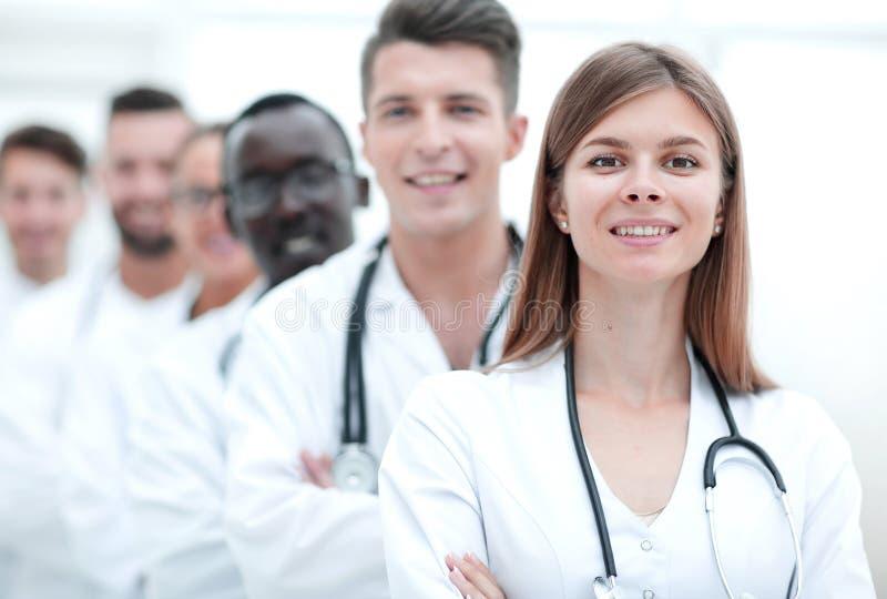 Χαμογελώντας γιατρός με τους συντροφικούς γιατρούς που στέκονται πίσω από την στοκ εικόνα