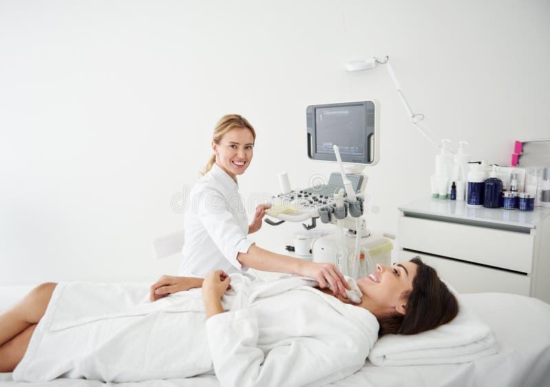 Χαμογελώντας γιατρός που κάνει τη δοκιμή υπερήχου θυροειδή για τη νέα γυναίκα στοκ εικόνα με δικαίωμα ελεύθερης χρήσης