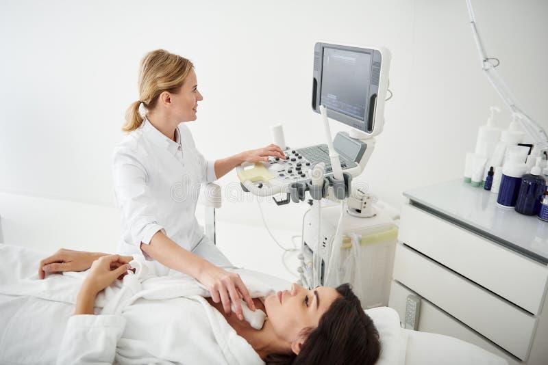 Χαμογελώντας γιατρός που κάνει τη δοκιμή υπερήχου θυροειδή για τη νέα γυναίκα στοκ φωτογραφία με δικαίωμα ελεύθερης χρήσης