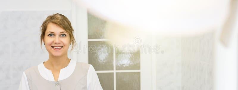 Χαμογελώντας γιατρός σε ένα φωτεινό ιατρικό γραφείο και ένας λαμπτήρας στο πρώτο πλάνο στοκ εικόνα