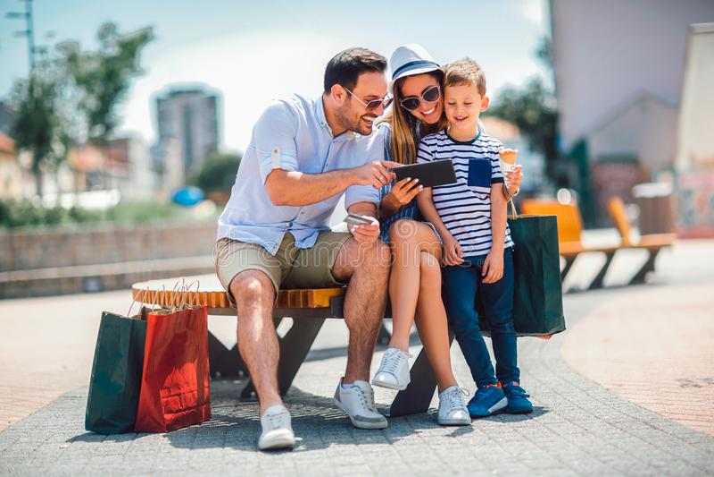 Χαμογελώντας γονείς και μικρό παιδί με το PC ταμπλετών και την πιστωτική κάρτα στοκ φωτογραφίες με δικαίωμα ελεύθερης χρήσης