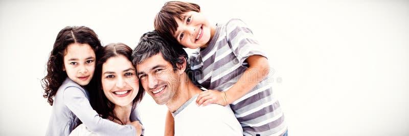 Χαμογελώντας γονείς που δίνουν στα παιδιά τους έναν γύρο σηκώνω στην πλάτη στοκ φωτογραφία με δικαίωμα ελεύθερης χρήσης