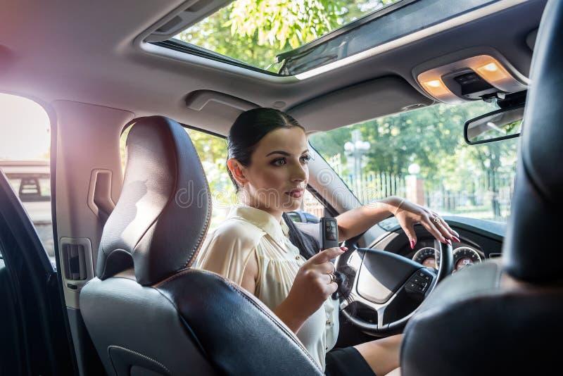 Χαμογελώντας γυναίκα μέσα στο αυτοκίνητο με το κλειδί από το στοκ φωτογραφίες