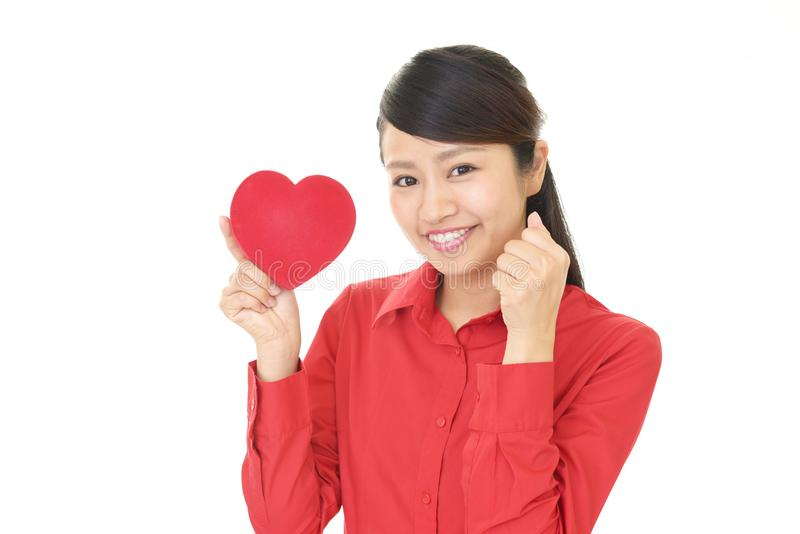 Χαμογελώντας γυναίκα με μια κόκκινη καρδιά στοκ φωτογραφία