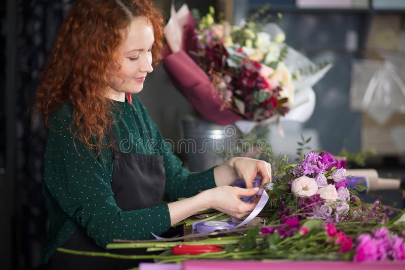 Χαμογελώντας γυναίκα με τα κόκκινα λουλούδια εκμετάλλευσης τρίχας που εξετάζει κατά μέρος το ανθοπωλείο στοκ εικόνες