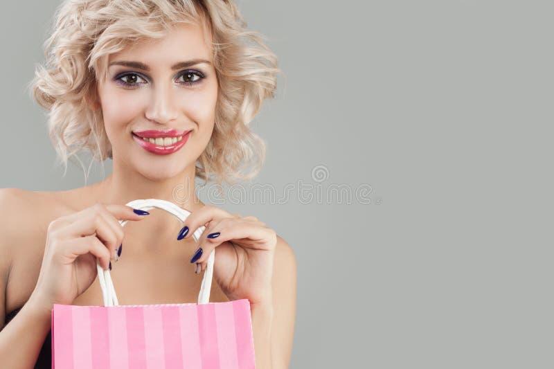 Χαμογελώντας γυναίκα με τις τσάντες αγορών Ευτυχές πρότυπο με το makeup και την ξανθή τρίχα στοκ εικόνα