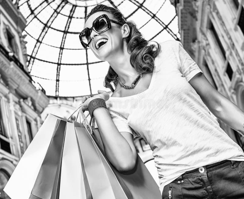 Χαμογελώντας γυναίκα με τις τσάντες αγορών σε Galleria Vittorio Emanuele στοκ εικόνες