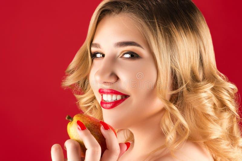 Χαμογελώντας γυναίκα με το αχλάδι διαθέσιμο στοκ εικόνα