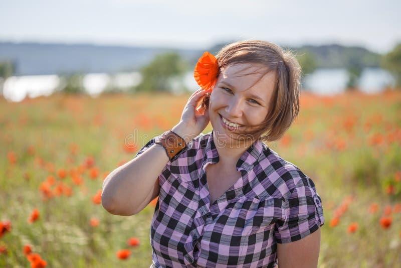 Χαμογελώντας γυναίκα με το λουλούδι παπαρουνών στην τρίχα της στοκ εικόνες