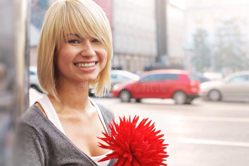 Χαμογελώντας γυναίκα με το λουλούδι στοκ φωτογραφία με δικαίωμα ελεύθερης χρήσης
