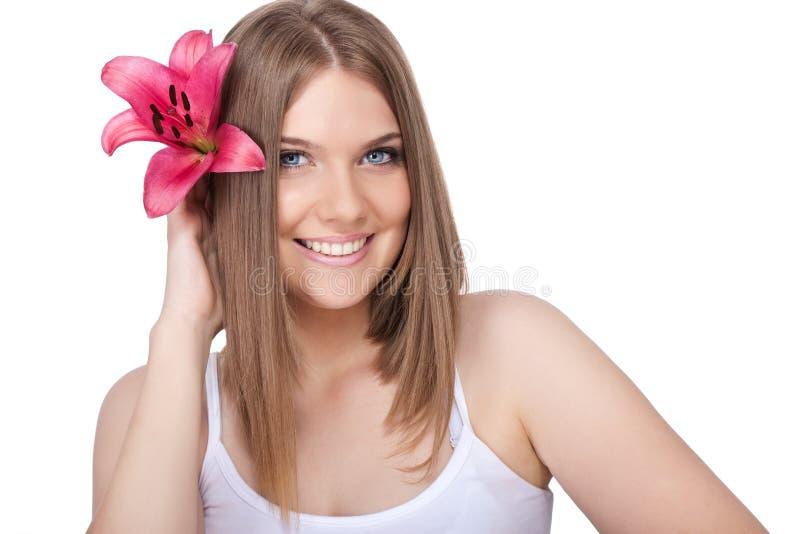 Χαμογελώντας γυναίκα με το ρόδινο κρίνο στοκ εικόνα με δικαίωμα ελεύθερης χρήσης