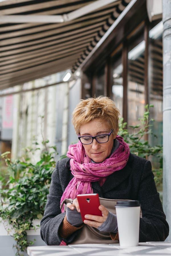 Χαμογελώντας γυναίκα με το τηλέφωνο στον καφέ στοκ εικόνα
