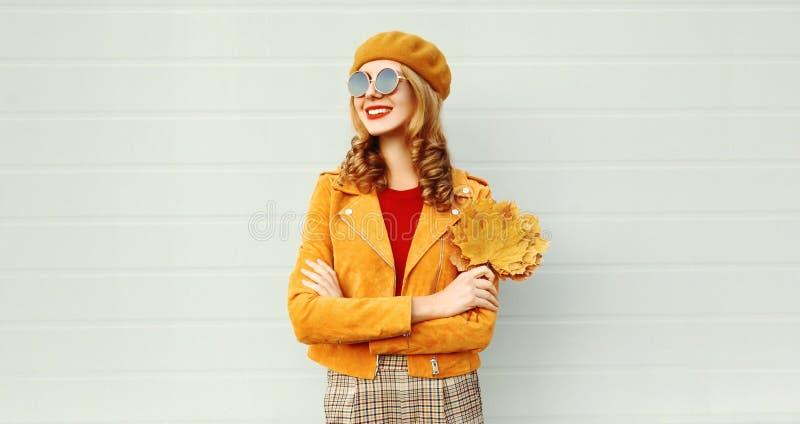 Χαμογελώντας γυναίκα πορτρέτου με τα κίτρινα φύλλα σφενδάμου που φορούν πορτοκαλί γαλλικό beret στην οδό πόλεων πέρα από τον γκρί στοκ φωτογραφία με δικαίωμα ελεύθερης χρήσης