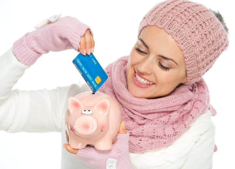 Χαμογελώντας γυναίκα που βάζει την πιστωτική κάρτα στη piggy τράπεζα στοκ φωτογραφία με δικαίωμα ελεύθερης χρήσης