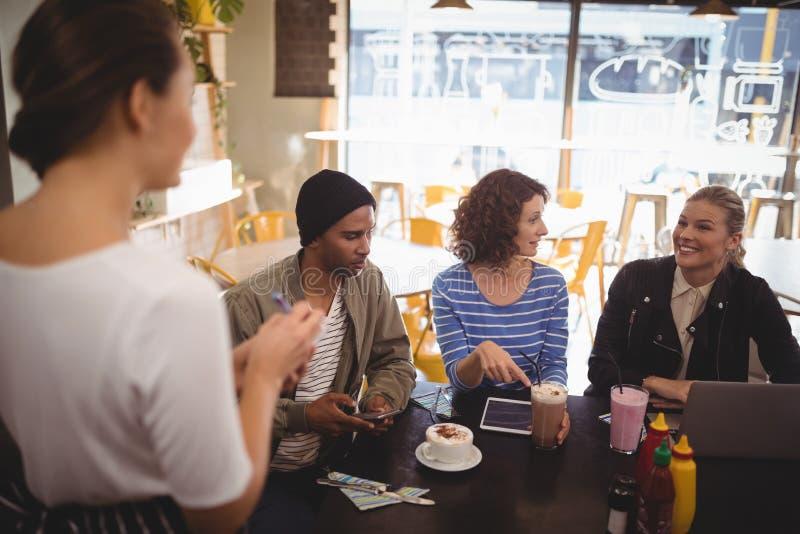 Χαμογελώντας γυναίκα που εγκαθιστά με τους φίλους που διατάζουν τα τρόφιμα στη σερβιτόρα στοκ εικόνες