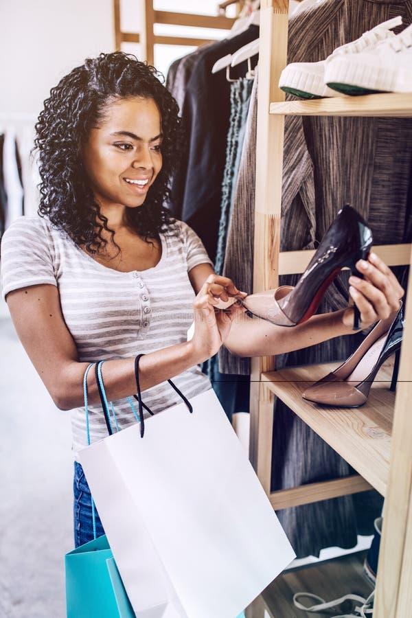 Χαμογελώντας γυναίκα που ελέγχει τα μοντέρνα τακούνια στο κατάστημα στοκ εικόνες με δικαίωμα ελεύθερης χρήσης