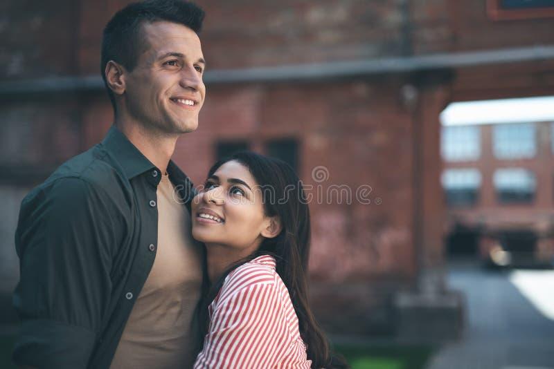 Χαμογελώντας γυναίκα που εξετάζει το φίλο αγκαλιάζοντας τον στοκ φωτογραφίες
