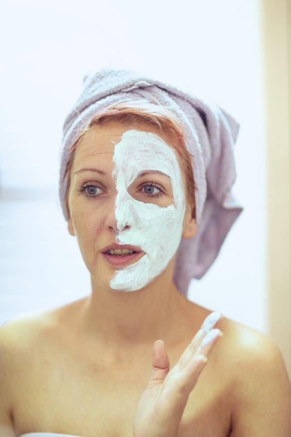 Χαμογελώντας γυναίκα που εφαρμόζει την του προσώπου μάσκα Επεξεργασίες ομορφιάς στοκ εικόνες
