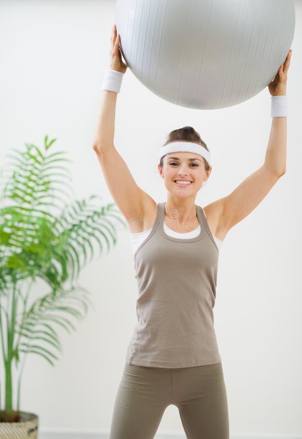 Χαμογελώντας γυναίκα που κάνει την άσκηση με τη σφαίρα ικανότητας στοκ εικόνα