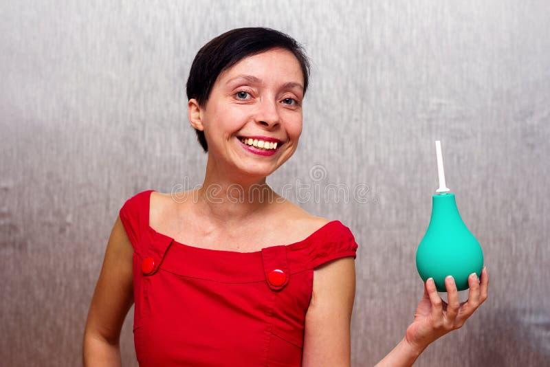 Χαμογελώντας γυναίκα που κρατά ένα enema στοκ εικόνα