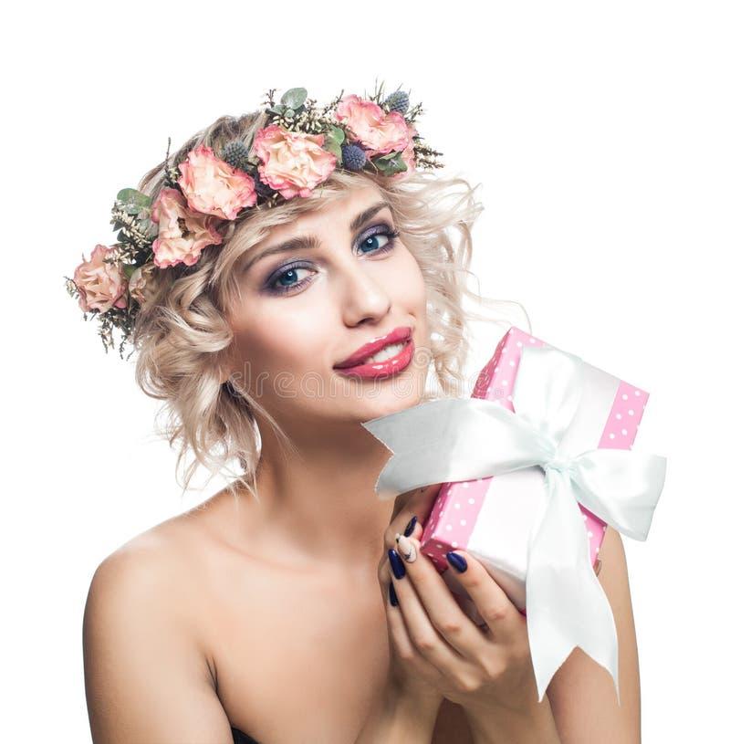 Χαμογελώντας γυναίκα που κρατά το ρόδινο κιβώτιο δώρων απομονωμένο στ στοκ φωτογραφίες