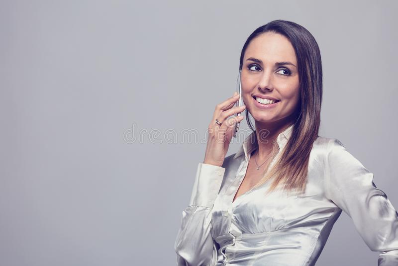 Χαμογελώντας γυναίκα που μιλά στο smartphone στοκ εικόνες