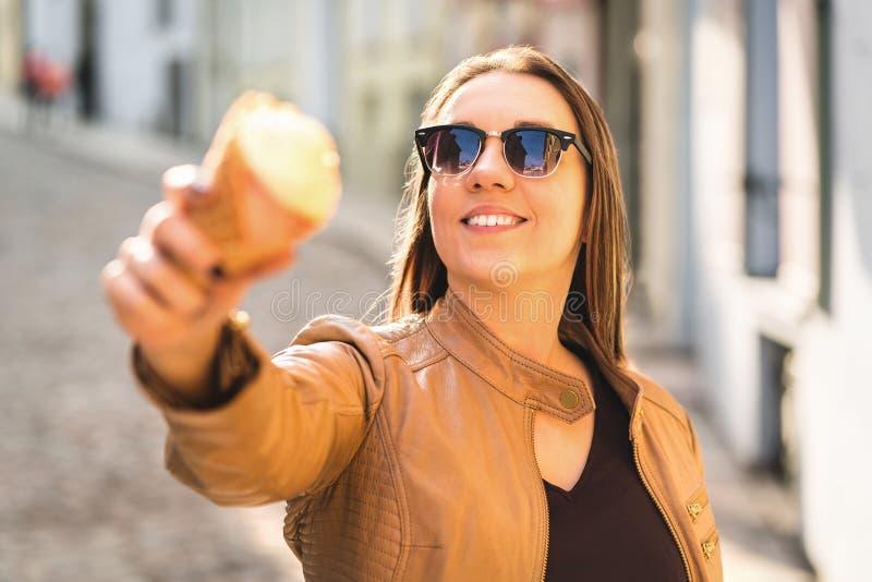 Χαμογελώντας γυναίκα που παρουσιάζει και που δείχνει κώνο παγωτού στη κάμερα στοκ εικόνα