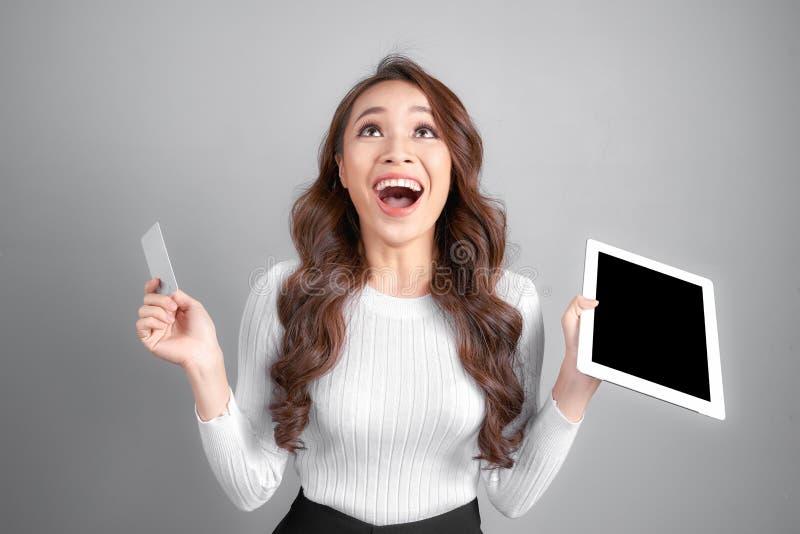 Χαμογελώντας γυναίκα που παρουσιάζει κενό PC ταμπλετών λαβής πιστωτικών καρτών υπό εξέταση, πέρα από το γκρίζο υπόβαθρο στοκ φωτογραφία με δικαίωμα ελεύθερης χρήσης