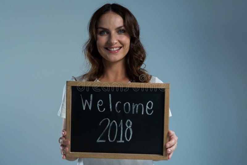 Χαμογελώντας γυναίκα που παρουσιάζει πλάκα με την υποδοχή 2018 κειμένων στο γκρίζο κλίμα στοκ φωτογραφίες
