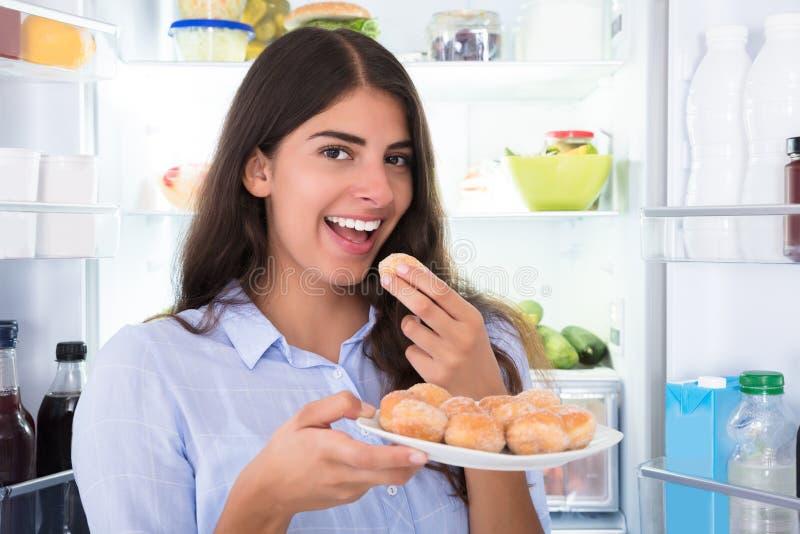 Χαμογελώντας γυναίκα που τρώει τα μπισκότα στο πιάτο στοκ φωτογραφία