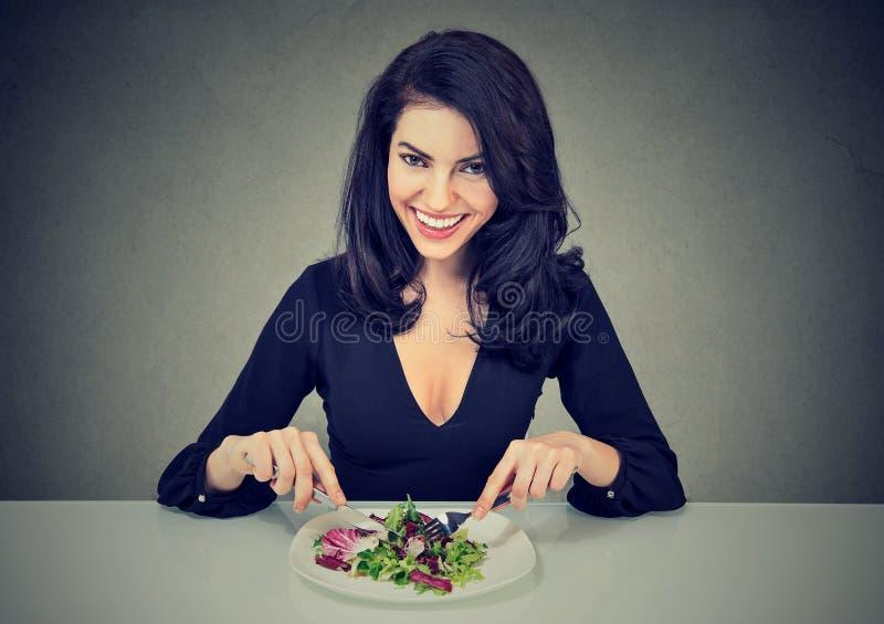 Χαμογελώντας γυναίκα που τρώει την υγιή σαλάτα στοκ εικόνα με δικαίωμα ελεύθερης χρήσης