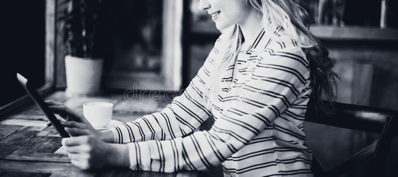 Χαμογελώντας γυναίκα που χρησιμοποιεί την ψηφιακή ταμπλέτα ενώ έχοντας τον καφέ στοκ εικόνες με δικαίωμα ελεύθερης χρήσης