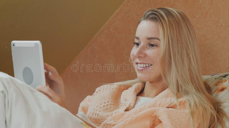 Χαμογελώντας γυναίκα που χρησιμοποιεί την ψηφιακή ταμπλέτα στο νοσοκομειακό κρεβάτι στοκ εικόνες με δικαίωμα ελεύθερης χρήσης