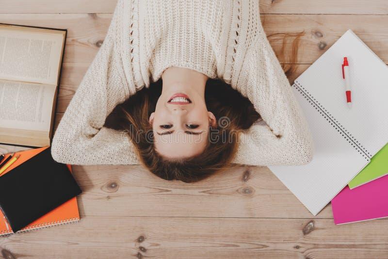 Χαμογελώντας γυναίκα σπουδαστών στο πάτωμα στοκ εικόνες με δικαίωμα ελεύθερης χρήσης